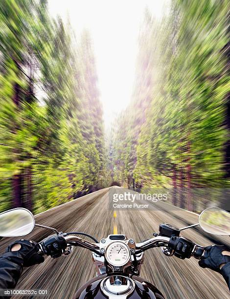 biker riding road in forest (personal perspective) - handlebar stock photos and pictures
