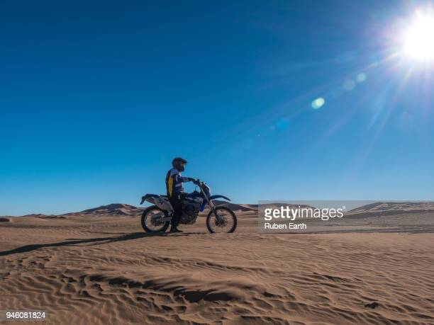 biker riding the sand dunes in the sahara desert - dakar stock pictures, royalty-free photos & images