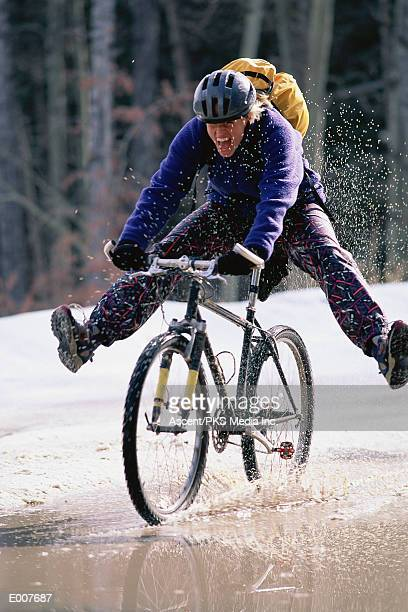 Biker riding through puddle in snow