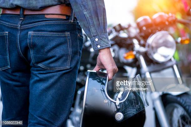 biker riding wear jeans with helmet and classic motorcycle blur background - jeans stock pictures, royalty-free photos & images