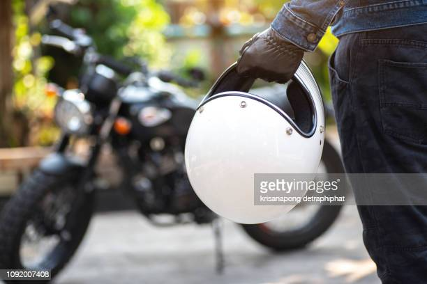 biker riding wear jeans with helmet and classic motorcycle blur background - crash helmet stock pictures, royalty-free photos & images