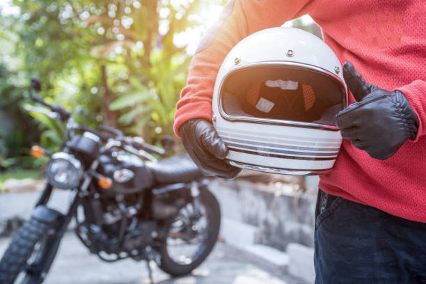 biker riding wear jeans with helmet and classic motorcycle