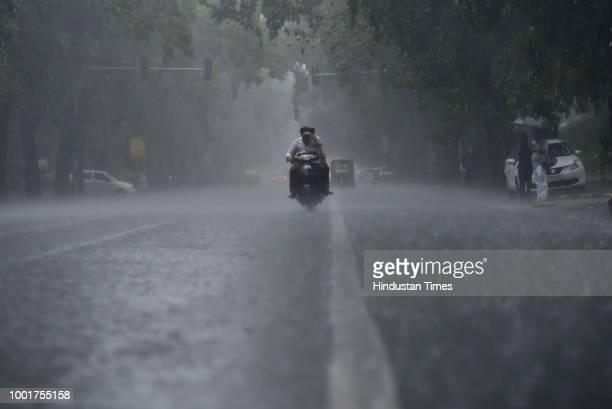 Biker shield his eyes with hands as it rains furiously near India Gate on July 13, 2018 in New Delhi, India. The national capital witnessed heavy...