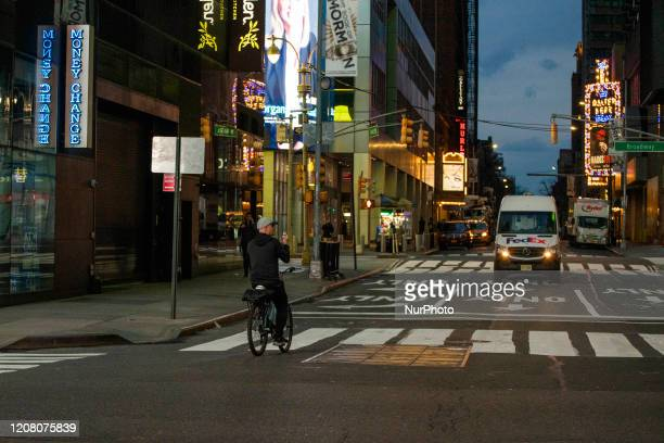 A biker takes a photo of a quiet Times Square on Friday March 2020 in New York NY The city officially announced the closure of all nonessential...