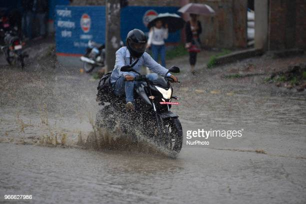 A Biker travelling through water logged road at Kathmandu Nepal on Sunday June 03 2018 Due to the poor water drainage management system yearly water...