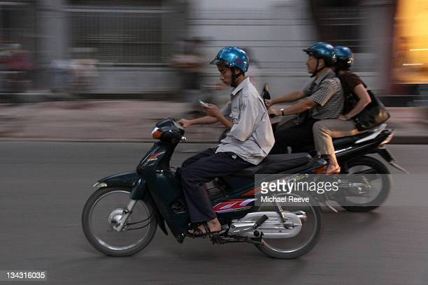 Biker uses his mobile phone while speeding along a street in Hanoi.