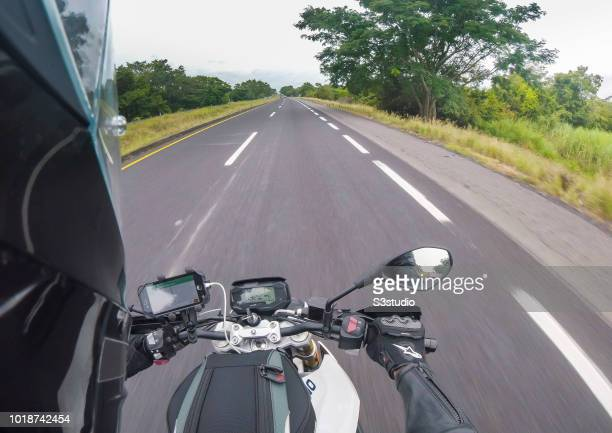 A biker using the mobile GPS navigation on his smart phone rides his motorcycle on the country road on 06 August 2018 in Guatemala