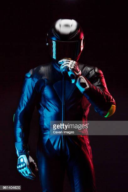 biker wearing helmet while standing against clear sky at night - crash helmet stock pictures, royalty-free photos & images