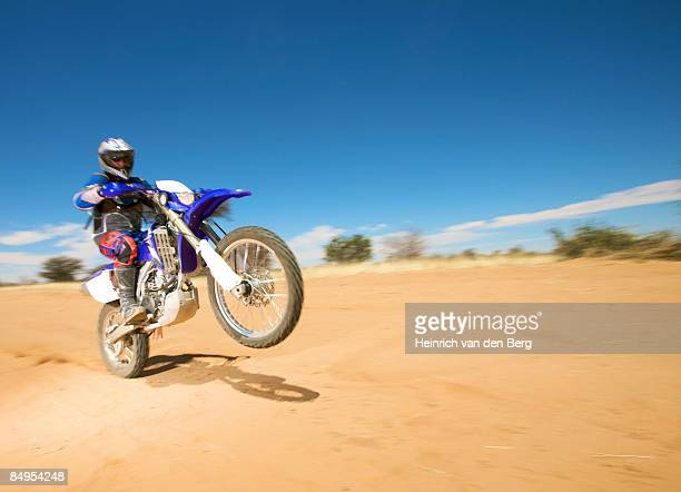 Biker wheelies on dirt road, Central Kalahari Desert, Botswana