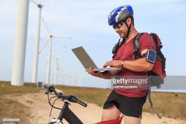Biker with backpack using laptop