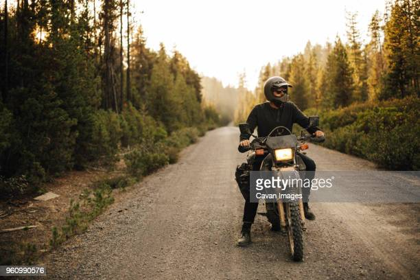 biker with motorcycle looking away on dirt road amidst forest - ecchi biker stock pictures, royalty-free photos & images