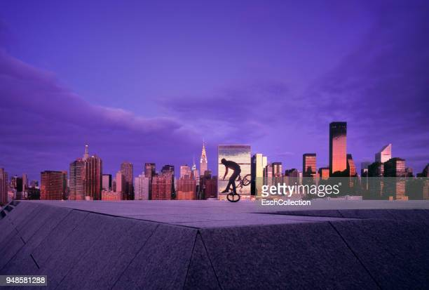 BMX Biker with skyline of New York at sunset