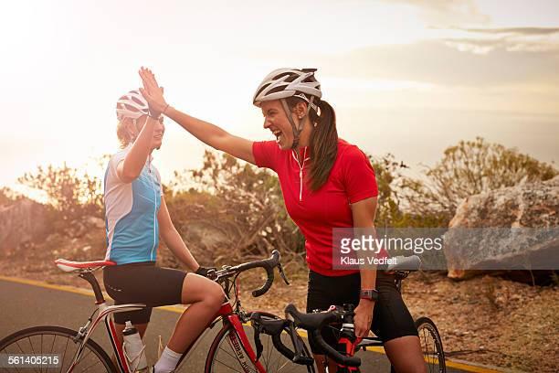 bikeriders & training partners doing high-five - radsport wettbewerb stock-fotos und bilder
