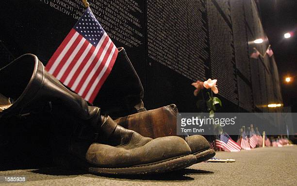 Bikers boots a wallet and the an American flag stand at rest at the base of The Vietnam Wall Experience a traveling replica of the Vietnam Memorial...