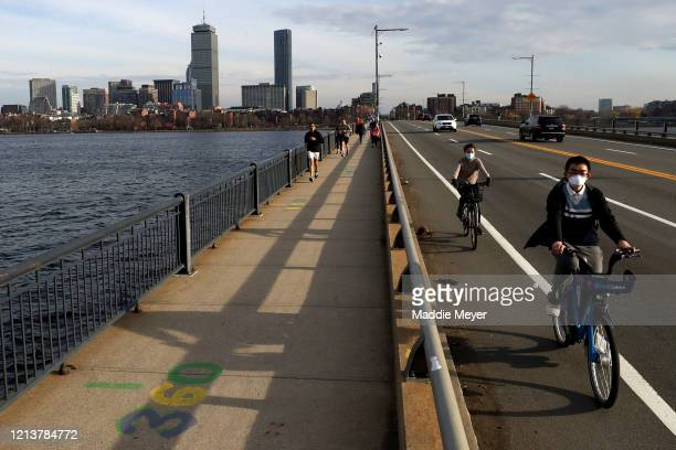 Bikers cross the Harvard Bridge connecting Boston and Cambridge on March 20, 2020 in Boston, Massachusetts. Local gyms and health clubs have been...