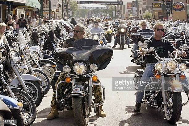 Bikers cruise during the annual Sturgis Motorcycle Rally August 7 2003 down Main Street in Sturgis South Dakota The weeklong rally attracts an...