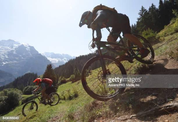 Bikers descend steep alpine slope