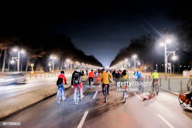 Bikers free riding down a city street at night.