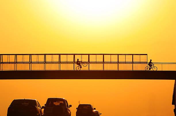Bikers on footbridge at sunset.