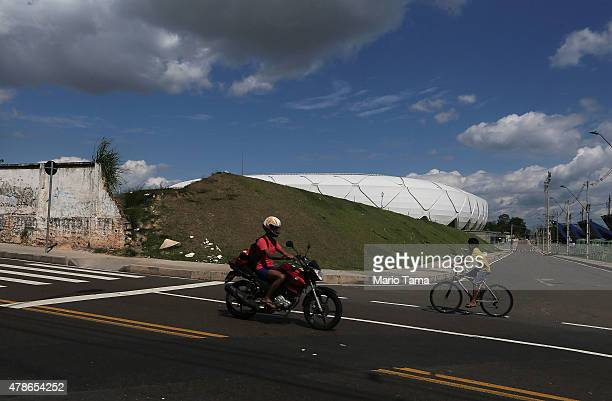 Bikers pass an old wall just outside an entrance road to the Arena de Amazonia June 26 2015 in Manaus Brazil The arena was constructed for $300...