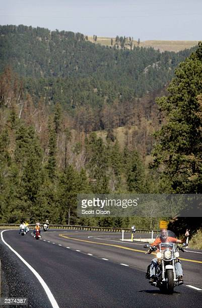 Bikers ride through the Black Hills National Forest on the outskirts of Sturgis South Dakota during the annual Sturgis Motorcycle Rally August 6 2003...