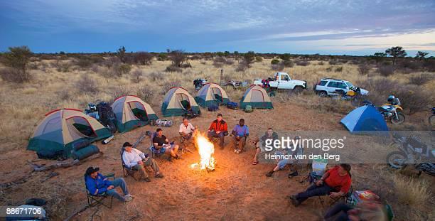bikers sit around a fire at camp, central kalahari desert, botswana - 囲む ストックフォトと画像