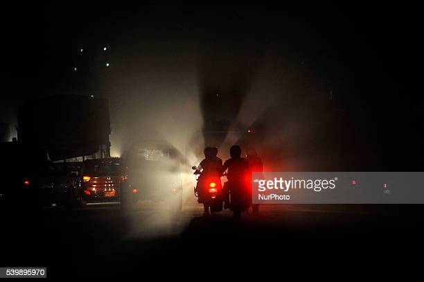 Bikers travelling through mass of dust particle which creates shadow of light scattered of dust particles at Balkhu Kathmandu Nepal on June 13 2016...