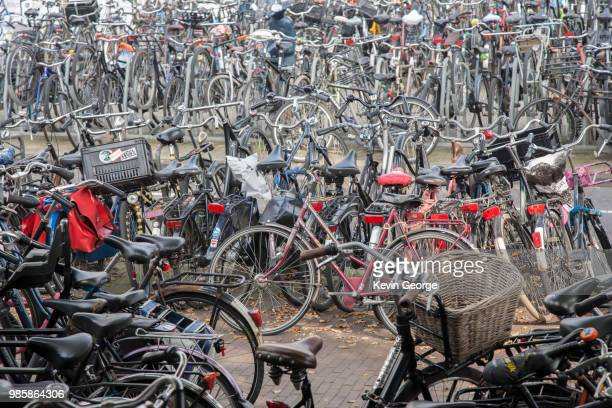 bikes parked at central station, amsterdam, holland - bicycle parking station stock photos and pictures