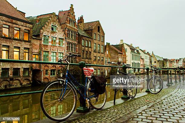 Bikes parked next to a water canal in Ghent, Belgium during a rainy winter day.