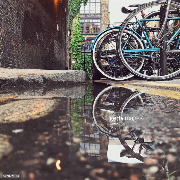 bikes reflected in a london street puddle - old london stock photos and pictures