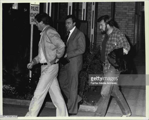 Bikie Raids -- Detectives lead a member of the Bandidos bikie gang into fairfeild police station at dawn today. September 21, 1984. .