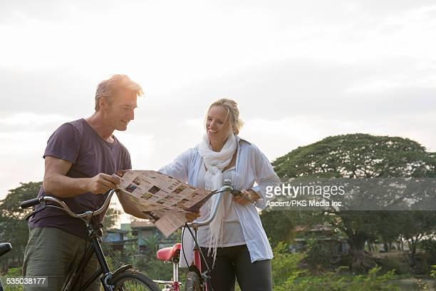 Biking couple examine map on rural journey