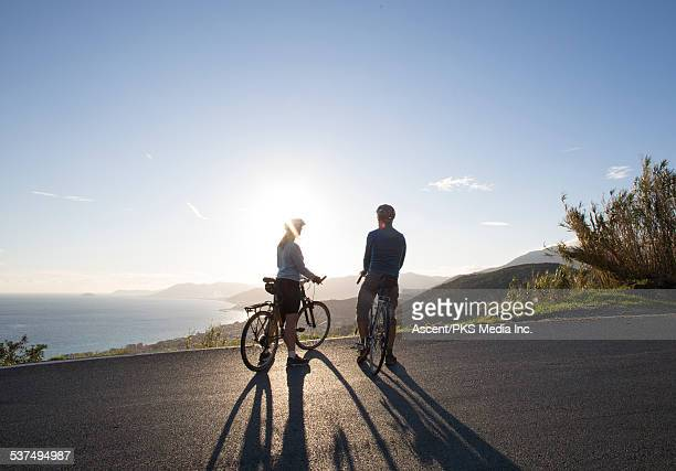 Biking couple pause to gaze out over sea