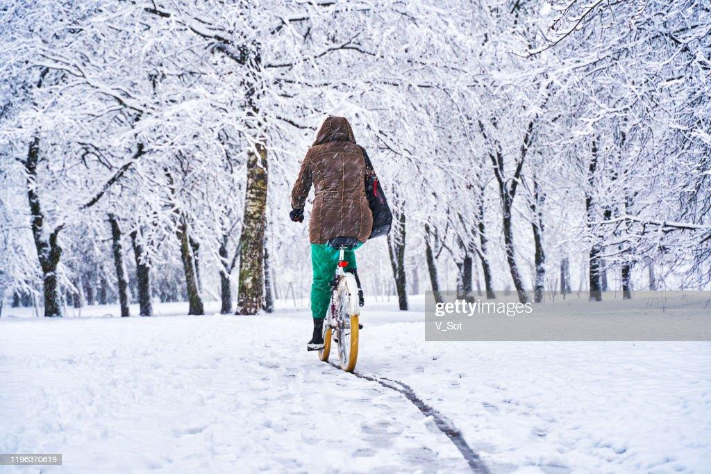 Fietsen in het besneeuwde Park : Stockfoto