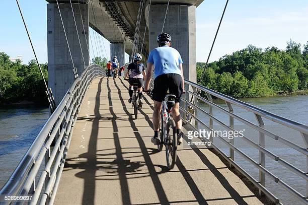 biking on bridge over james river in richmond - richmond virginia stock pictures, royalty-free photos & images