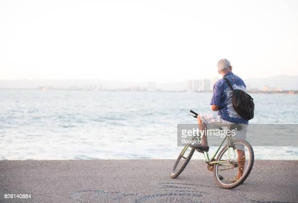 Ciclismo a Senior Hombre mirando al mar vista de Malecón Puerto Vallarta
