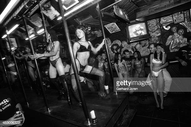 Bikini clad dancers at the Tahitian Queen GoGo bar on the Beach Road in Pattaya Customers can take a girl away from the bar for 500 Baht known as a...
