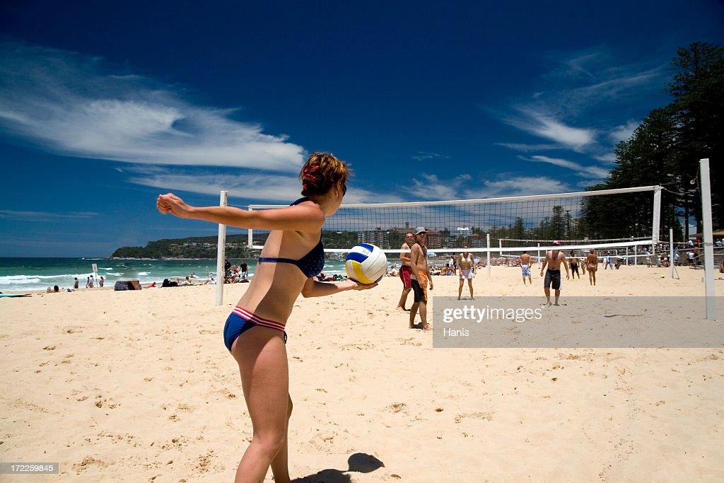 A bikini clad woman prepares to serve in beach volleyball : Stock Photo