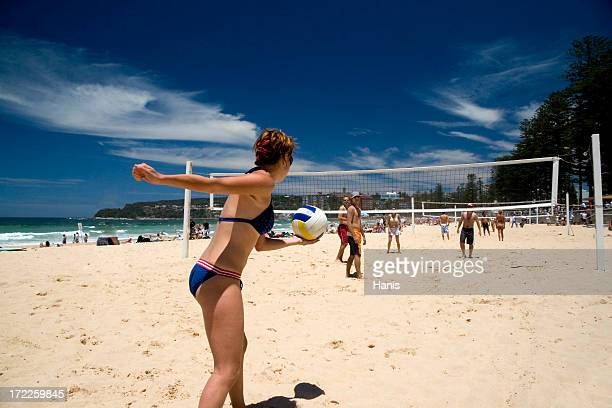 A bikini clad woman prepares to serve in beach volleyball