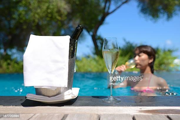 Fille Bikini buvant du Champagne dans la piscine