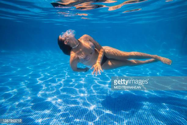 bikini girl swimming underwater dance in a blue tiles pool on summer vacation - underwater stock pictures, royalty-free photos & images