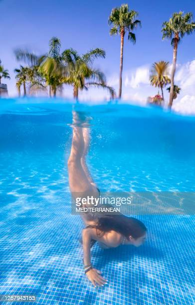 bikini girl swimming underwater handstand in a blue swimming pool - women wearing see through clothing stock pictures, royalty-free photos & images