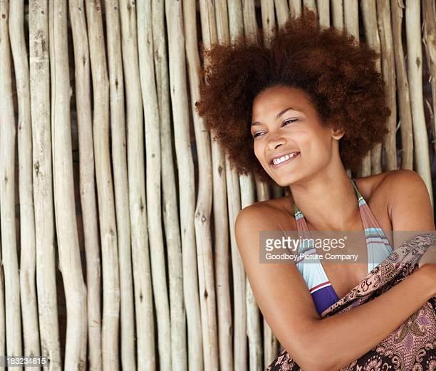 Bikini model smiles and leans against bamboo wall