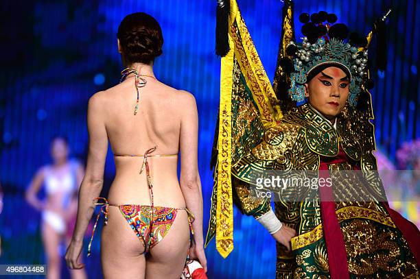 A bikini model walks the runway with a male role dressed in costumes during an luxury brand show at Shandong Grand Theater on November 11 2015 in...