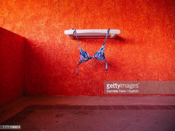 bikini top hanging against orange wall - bikini top stock pictures, royalty-free photos & images