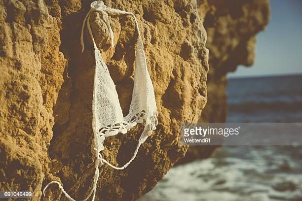 Bikini top hanging on a rock on the beach