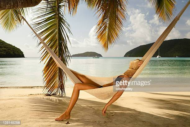 bikini woman napping in a hammock at the Caribbean beach