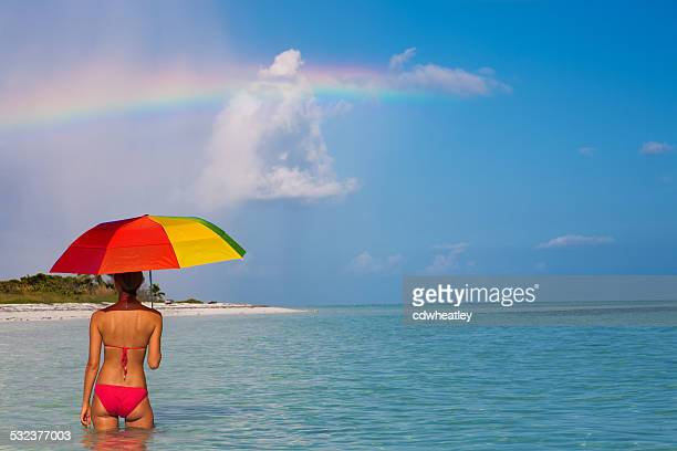 bikini woman with an umbrella watching a rainbow in Florida