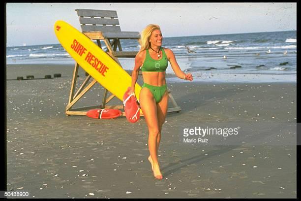 Bikiniclad lifeguard Jennifer Keefe walking away fr her post on beach