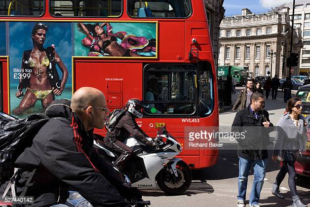Bikiniwearing model on a bus ad and crossing pedestrians in a busy London street Waiting for a green light a cyclist in the foreground a motorcyclist...